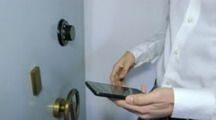 Businessman insert the combination to the safe, writing cellphone - stock footage