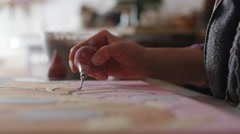 Ceramic maker filling pencil strokes on terracotta with rubber bulb extreme Stock Footage
