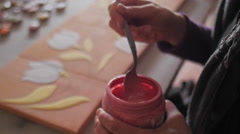 Ceramic maker mixing color enamel in plastic jar - stock footage