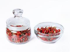 Dried wild rose in a glass jar, rosehips dried in a glass bowl on white basis Stock Photos