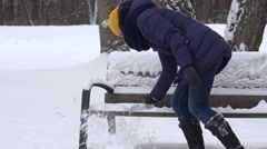 Woman girl clean snow from wooden bench in park and sit with smile. 4K Stock Footage