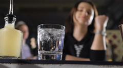 Attractive girl in a good mood, sitting at the bar, with a glass in her hand Stock Footage