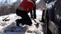 Worker removing snow with a shovel under the a car stuck in drifts of snow Stock Footage