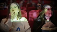 Teenage girls watching movie in cinema - stock footage