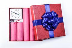 Bomb sticks of dynamite, in a gift box with a blue ribbon with clockwork. Stock Photos