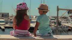 little boy and girl sitting on a pier Yacht Club - stock footage