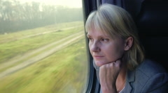 Thoughtful woman looking out the window of a train traveling Stock Footage