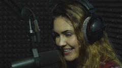 Beautiful radio DJ smiling on camera Stock Footage