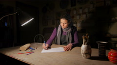 Ceramic maker designing artwork with pencil in her atelier slide-cam wide shot Stock Footage