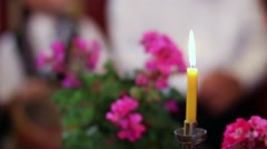 Yellow candle burning flame, situated between potted with geraniums purple Stock Footage