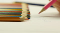 Woman taking pink pencil and drawing on white paper Stock Footage