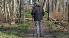 Hiker with walking sticks on path in the park Stock Footage