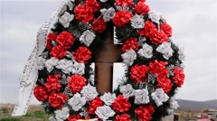 Grave with wooden cross with flowers and wreaths in memory of the deceased filed Stock Footage