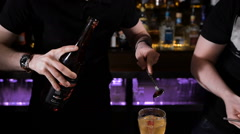 Slender young bartender in a stylish shirt. Adds syrup in a cocktail. Bar Stock Footage