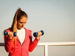 Woman doing sports outdoors with dumbbells - stock photo