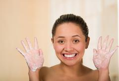 Youg woman with bare skin shoulders holding up creamy hands and smiling to Stock Photos