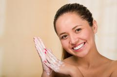 Young woman with bare skin shoulders, creamy hands, holding fingers together and Stock Photos