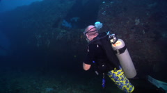 Male model scuba diver looking around in lagoon entrance channel in Palau Stock Footage