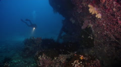 Ocean scenery exploring along the hull and rudder toward divers doing likewise, Stock Footage