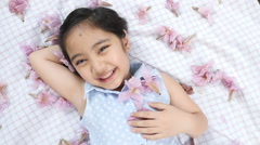 Little Asian child laying down on the floor with falling flowers - stock footage