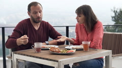 Young couple fighting, arguing during breakfast on terrace - stock footage