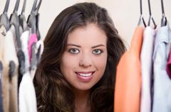 Attractive brunette standing with head in between clothes at clothing rack Stock Photos