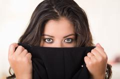 Headshot attractive brunette facing camera covering half her face with black - stock photo