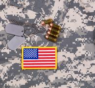 USA flag patch, ID tags, bullets on military battle dress uniform. Stock Photos