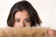 Headshot attractive brunette facing camera covering half her face with brown fur - stock photo