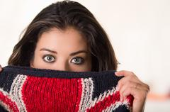 Headshot attractive brunette facing camera covering half her face with british - stock photo