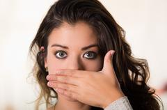 Headshot attractive brunette facing camera covering half her face using one hand - stock photo