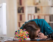 Brunette woman sleeping at desk with computer and molecular model kit on table Stock Photos