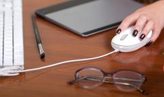 Hand clicking on computer mouse, wooden desk surface with glasses, tablet and Kuvituskuvat