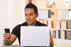 Young hispanic man sitting by desk working on white laptop and looking at mobile - stock photo