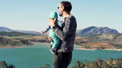 Young father standing with son looking on beautiful landscape Stock Footage