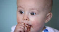 messy baby eating cookie - stock footage
