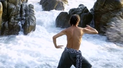 Caucasian man practicing  tai chi inside pacific ocean waves Stock Footage