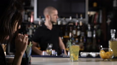 Handsome bartender making cocktails for beautiful women in a classy bar - stock footage