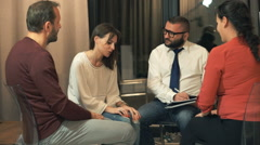People sitting in circle during therapy at psychologist Stock Footage