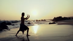 Caucasian man practicing  tai chi on the beach at sunset Stock Footage