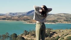 Woman enjoying sunny day and stretching her arms in the country Stock Footage
