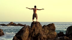 caucasian man practicing  tai chi on the rocks in front the pacific ocean - stock footage