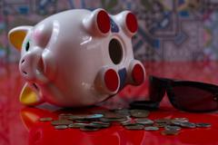 Opened piggy bank with black sunglasses and rolls cash - stock photo
