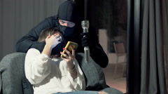 Young woman sitting with smartphone in her home when man in balaclava attack her Stock Footage