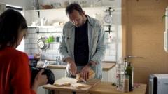 Woman record film while her boyfriend prepare sandwich in the kitchen - EDITORIA Stock Footage