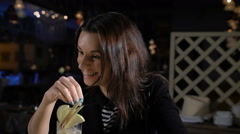 The girl in the bar drinking cocktails and laughs. Attractive brunette in a Stock Footage