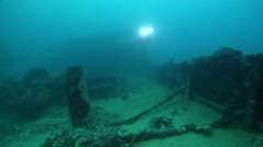 Ocean scenery diver exploring the deck, on silty World War II wreck, HD, UP33551 Stock Footage