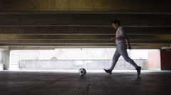 Football player doing kick up tricks in an urban city environment - stock footage
