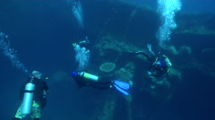 Group of scuba divers swimming on lagoon World War II wreck in Palau Stock Footage