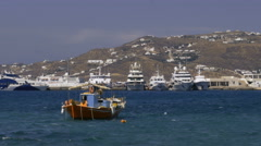 Small boat and luxury yachts in harbor Mykonos Greece - stock footage